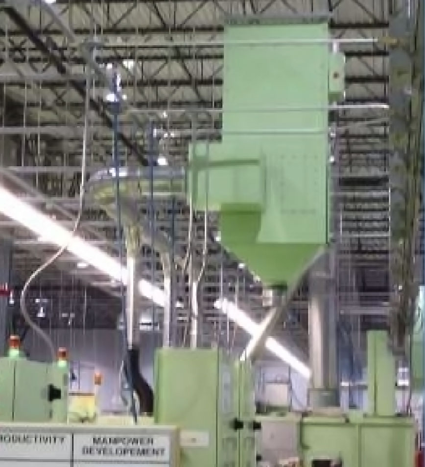 vertical cartridge media collector mounted above machinery in production environment